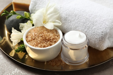 Spa composition with sea salt on golden tray, closeup