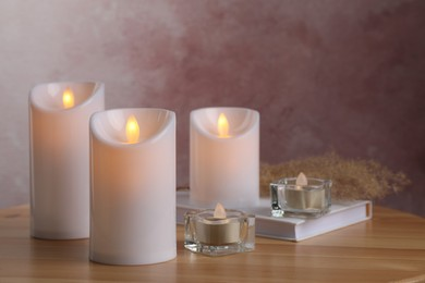 Glowing decorative LED candles on wooden table