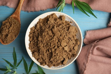 Hemp protein powder and fresh leaves on light blue wooden table, flat lay
