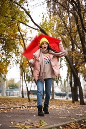 Woman with red umbrella caught in gust of wind outdoors