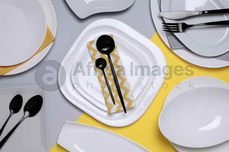 Different plates and cutlery on color background, flat lay