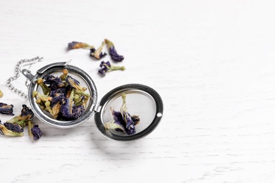 Dry organic blue Anchan and metal infuser on white wooden table, space for text. Herbal tea
