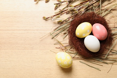 Flat lay composition with painted Easter eggs on wooden table, space for text