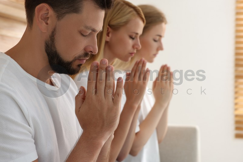 Group of religious people praying together indoors. Space for text