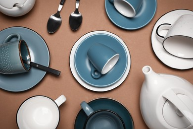 Different cups and teapot on brown background, flat lay