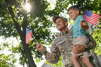 Soldier and his little son with American flags outdoors, low angle view. Veterans Day in USA