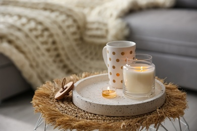 Cup of drink and burning candles on stand in room, space for text. Interior elements