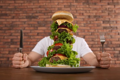 Hungry man with cutlery and huge burger at wooden table