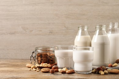 Different nut milks on wooden table. Space for text