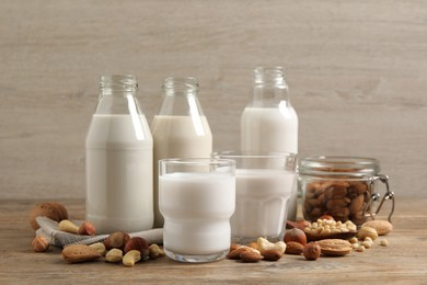Different nut milks in glassware on wooden table