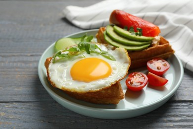 Delicious Belgian waffle with fried egg, arugula and vegetables on grey wooden table, closeup