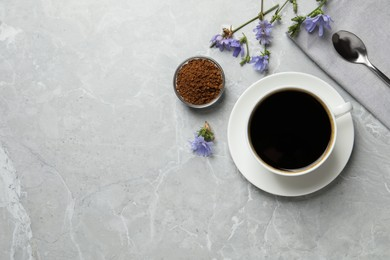 Cup of delicious chicory drink, granules and flowers on light grey marble table, flat lay. Space for text
