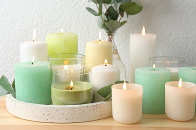 Set of burning candles on table near white wall