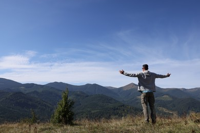 Man enjoying picturesque view of mountain landscape on sunny day