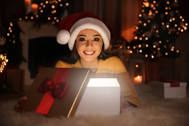 Young woman wearing Santa hat opening Christmas gift on floor at home