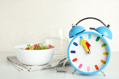 Alarm clock with salad on white table. Meal timing concept
