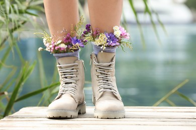 Woman standing on wooden pier with flowers in socks outdoors, closeup