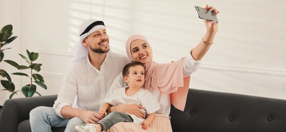 Happy Muslim family taking selfie on sofa at home. Banner design