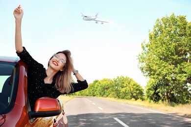 Young woman leaning out of car window and airplane in sky. Summer vacation