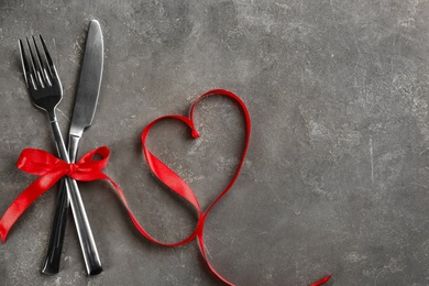 Cutlery set and red ribbon on grey background, flat lay with space for text. Valentine's Day dinner