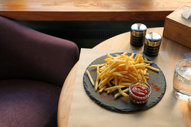 Tasty French fries with red sauce served on table in cafe
