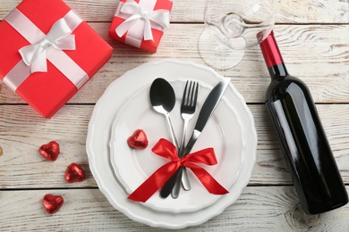 Beautiful table setting for Valentine's Day dinner on white wooden background, flat lay