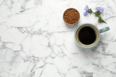 Cup of delicious chicory drink, granules and flowers on white marble table, flat lay. Space for text