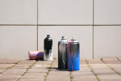 Used cans of spray paint on pavement near white tile wall outdoors, space for text. Graffiti supplies