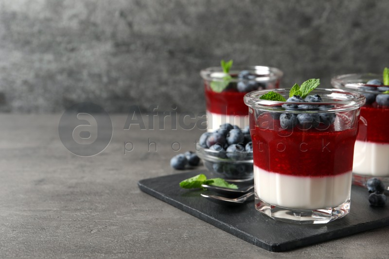 Delicious panna cotta with fruit coulis and fresh blueberries served on grey table. Space for text