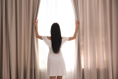 Woman opening window curtains at home in morning, back view