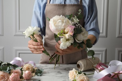 Florist creating beautiful bouquet at white marble table, closeup