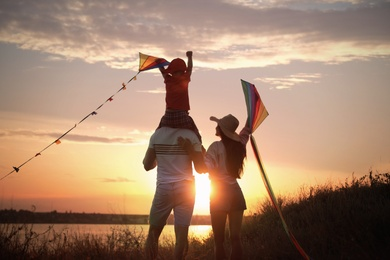 Parents and their child playing with kites outdoors at sunset, back view. Spending time in nature