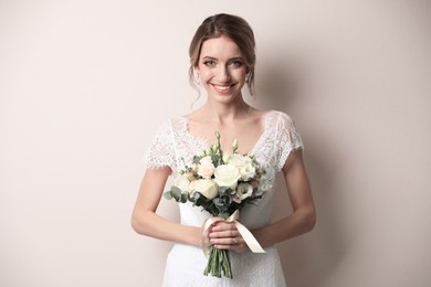 Young bride with beautiful wedding bouquet on beige background