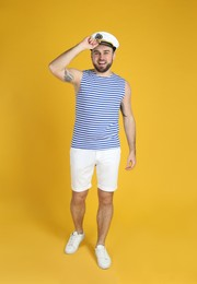 Full length portrait of sailor on yellow background