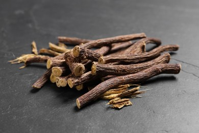 Dried sticks of liquorice root on black table