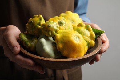 Woman with wooden bowl of fresh ripe pattypan squashes on grey background, closeup