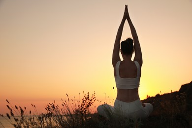 Woman meditating outdoors at sunset, back view. Space for text