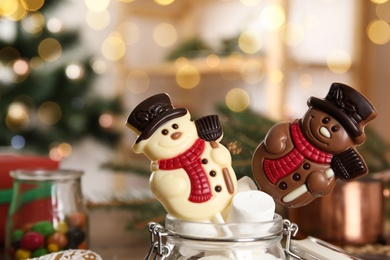 Funny chocolate snowmen candies in glass jar with marshmallows, closeup