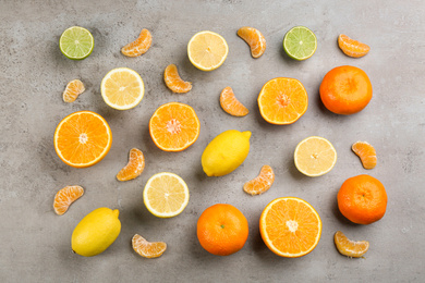 Flat lay composition with tangerines and different citrus fruits on grey background