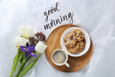 Delicious coffee, cookies, flowers and GOOD MORNING wish on white cloth, flat lay