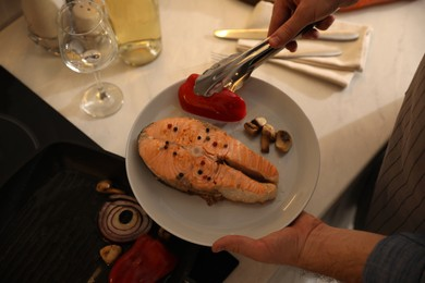 Man holding plate with tasty salmon steak and vegetables cooked on frying pan, above view