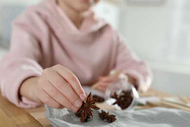 Little girl working with natural materials at table indoors, closeup. Creative hobby