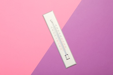 Weather thermometer on color background, top view
