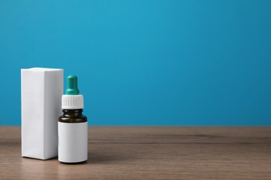 Nasal drops with blank label and package on wooden table against light blue background. Space for text