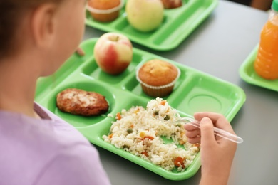 Girl sitting at table and eating healthy food during break at school, closeup