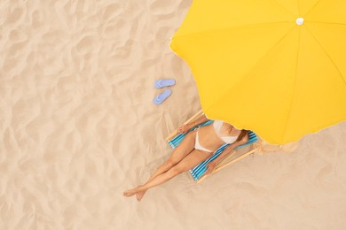 Woman resting in sunbed under yellow beach umbrella at sandy coast, aerial view. Space for text