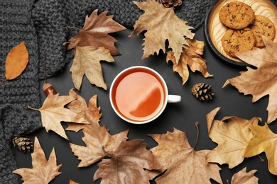 Flat lay composition with hot cozy drink and autumn leaves on dark background