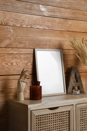 Empty frame with other decor on table near wooden wall. Mockup for design