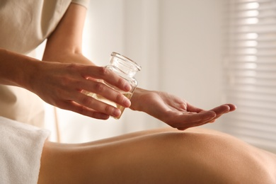 Young woman receiving back massage with oil in spa salon, closeup