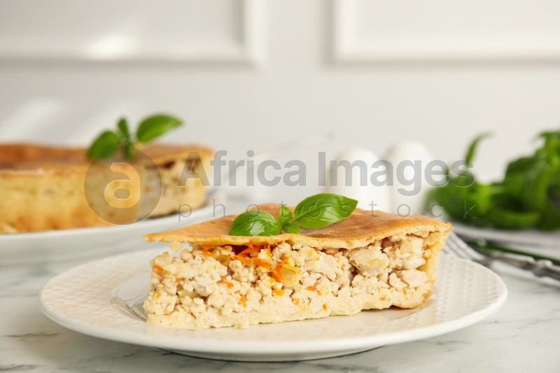 Piece of delicious pie with meat and basil on white marble table
